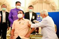 Statsminister Prayuth ble vaksinert av ledende vitenskapsmann Dr. Yong Poovorawan i mars. Helseminister Anutin står bak i lilla. De fleste andre thaier venter fortsatt på vaksine.